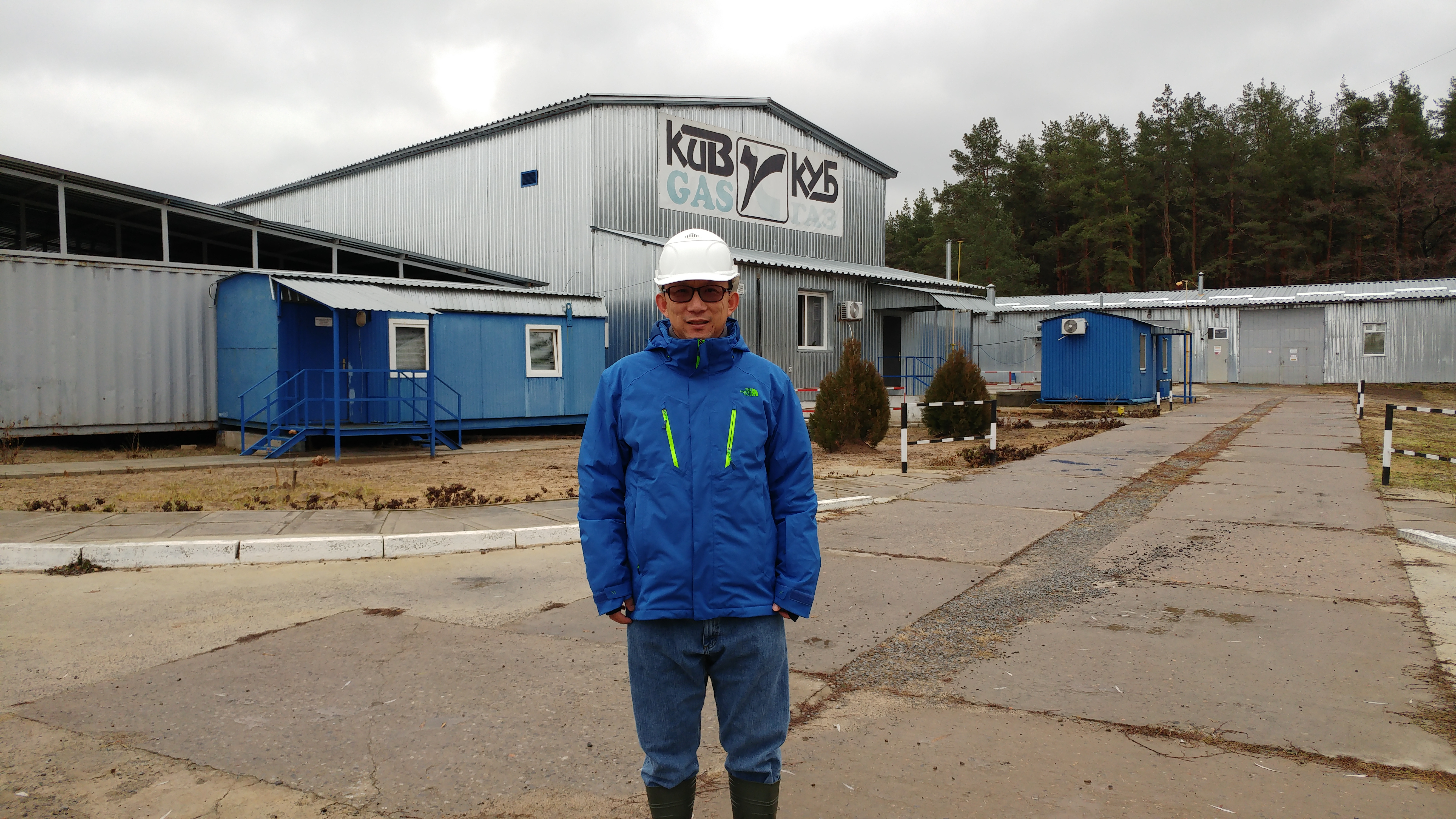 Chen standing in front of the gas plant
