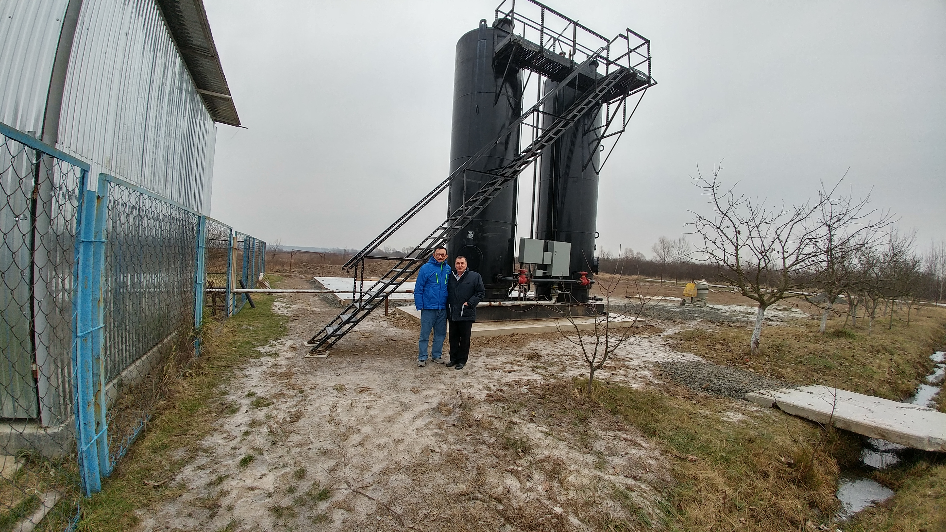 Mikhail Vuksta and Chen standing in front of the nitrogen processing unit.  			It is ready to go in a couple of months to inject natural gas into the pipeline.